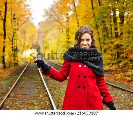 Young happy woman in autumn park - stock photo