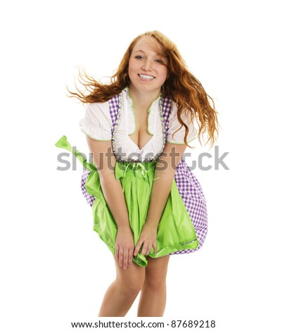 young happy woman in bavarian dress handling with wind on white background - stock photo