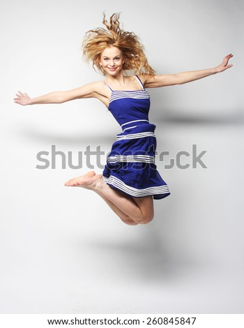 young happy woman in blue dress jumping over white background - stock photo
