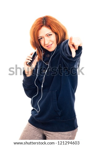 Young happy woman in blue hoodie holding smartphone, listening music and pointing at you, isolated on white background. - stock photo