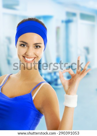 Young happy woman in blue sportswear showing okay hand sign gesture, at fitness club or center. Beauty and health concept. - stock photo