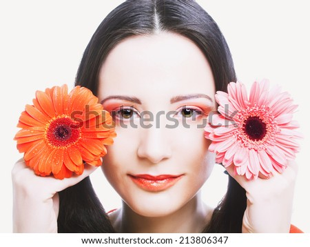 Young happy woman in orange dress posing with flowers - stock photo