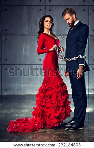 Young happy woman in red dress holding man on heavy chain. Elegant evening clothing. - stock photo