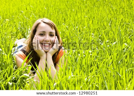 Young happy woman in the grass - stock photo