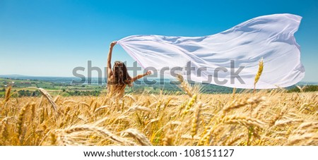 Young happy woman in wheat field with fabric. Summer set - stock photo