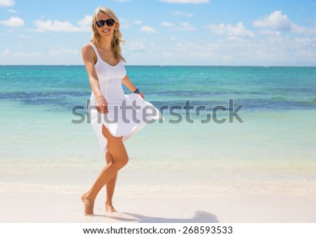 Young happy woman in white dress on the beach - stock photo