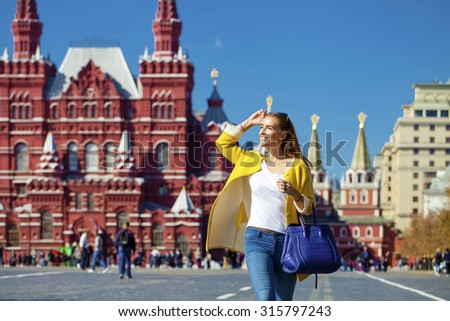 Young happy woman in yellow coat walks on the Red Square in Moscow - stock photo