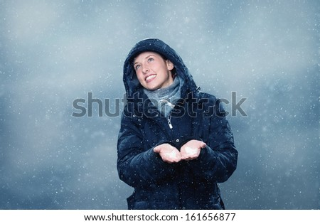 young happy woman is happy about the first snow - stock photo