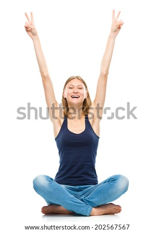Young happy woman is raised her hands up in joy showing victory sign, isolated over white - stock photo