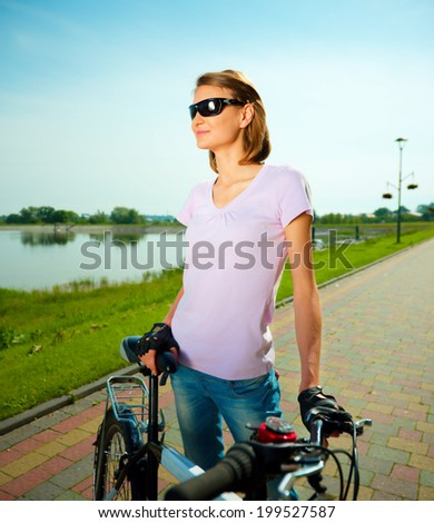 Young happy woman is standing behind bicycle, outdoor shoot - stock photo
