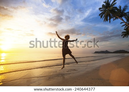 Young happy woman jumping on the sea coast during the amazing sunset. - stock photo
