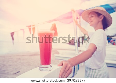 Young happy woman looking far away near sand beach with fresh watermelon juice (intentional bright sun and vintage color, lens focus on glass) - stock photo