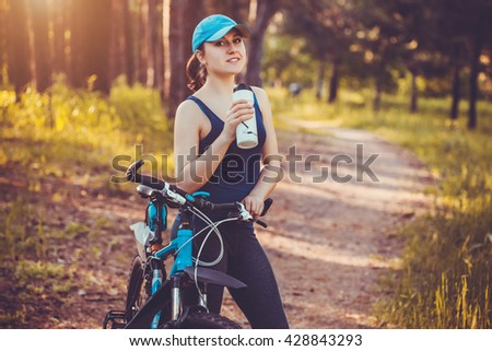 Young happy woman on bike standing on a hill road enjoying beautiful view summer sunny day resting drinking water - stock photo