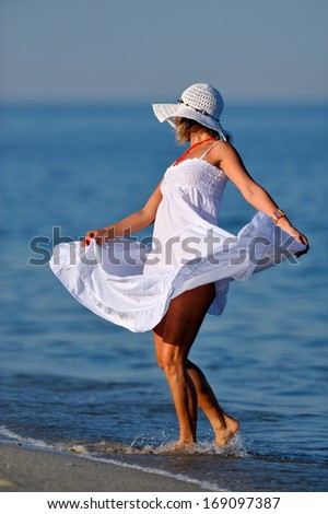 young happy woman on the beach in summer - stock photo