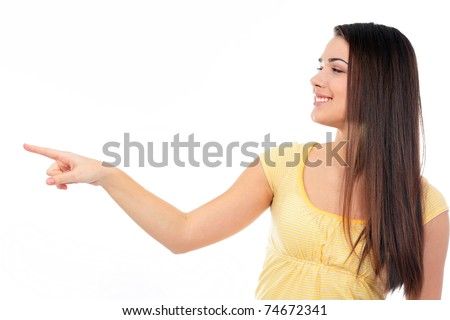 Young happy woman pointing to the side at copyspace - stock photo