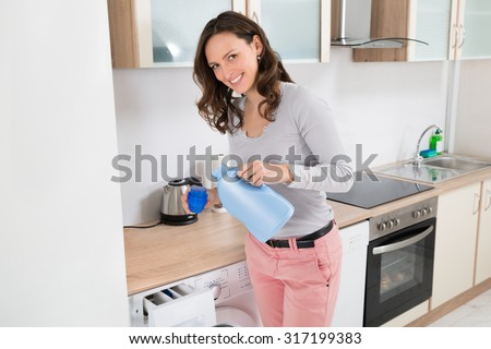 Young Happy Woman Pouring Liquid Detergent In The Bottle Cap - stock photo