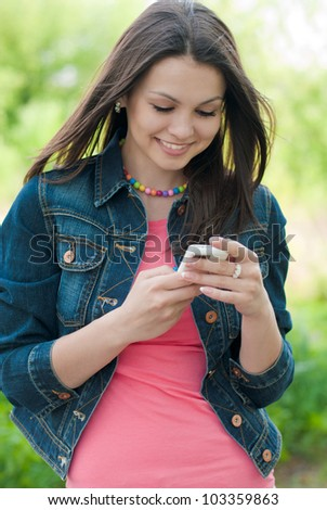 Young happy woman reading message on mobile phone outdoors - stock photo
