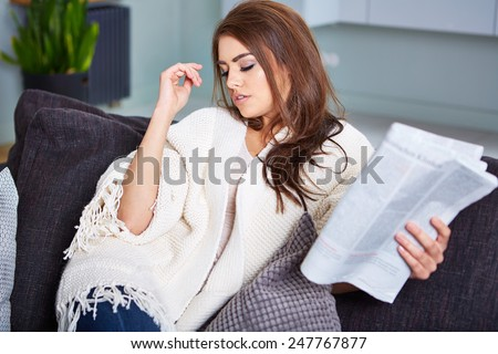 Young Happy Woman Reading Newspaper On Couch - stock photo