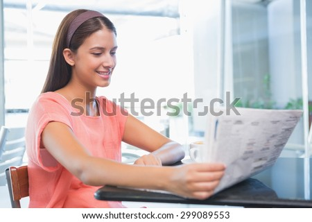 Young happy woman reading the newspaper in the cafe - stock photo