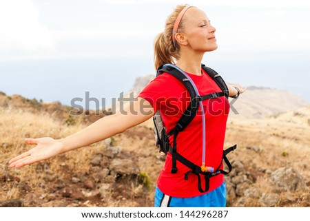 Young Happy Woman Runner Enjoying Summer Day in Mountains with Arms Outstretched. Motivation and Inspiration Fitness Concept. Female jogger exercising outdoors in nature, La Gomera Canary Islands. - stock photo