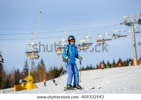 Young happy woman skier skiing downhill at ski resort on a sunny day against ski-lift. Girl is wearing blue jacket helmet, goggles and backpack. Carpathian Mountains, Bukovel - stock photo