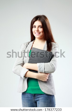 Young happy woman standing with book on gray background - stock photo