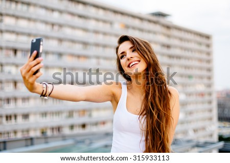 Young happy woman taking selfie on the rooftop - stock photo