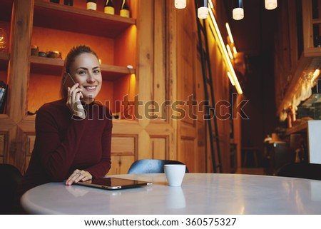 Young happy woman talking on mobile phone with her boyfriend while relaxing in cozy cafe bar after walking, smiling cheerful female speaking on cell telephone while sitting in modern coffee shop  - stock photo