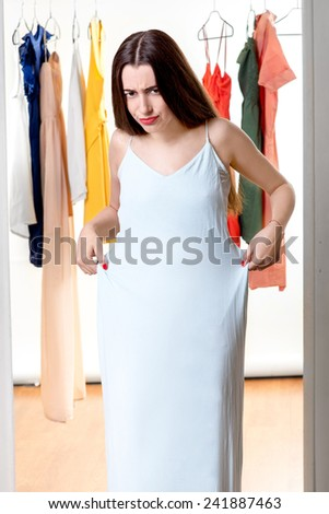 Young happy woman trying on new dress to wear in front of the wardrobe - stock photo