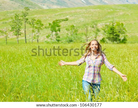 Young happy woman walking on wheat field, cute teen runs on green grass field, carefree girl enjoying peaceful countryside nature, beautiful smiling female have recreation in park, freedom concept - stock photo