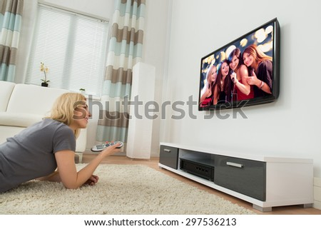 Young Happy Woman Watching Television While Lying On Carpet At Home - stock photo
