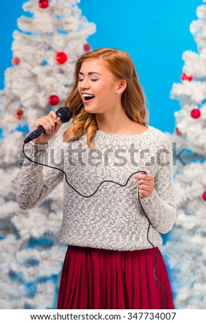 Young happy woman with a microphone sings a song during the celebration of Christmas, Christmas tree background - stock photo