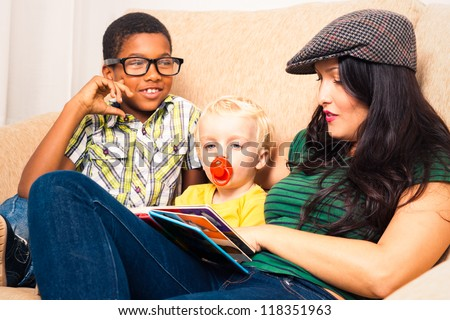 Young happy woman with children reading book and relaxing on sofa. - stock photo