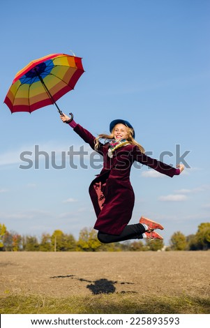 Young happy woman with colorful umbrella jumping high on empty autumn field copy space background - stock photo