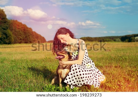 Young happy woman with dog on the meadow at sunset - stock photo