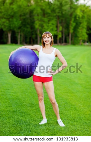 Young happy woman with fitness ball, outdoor - stock photo