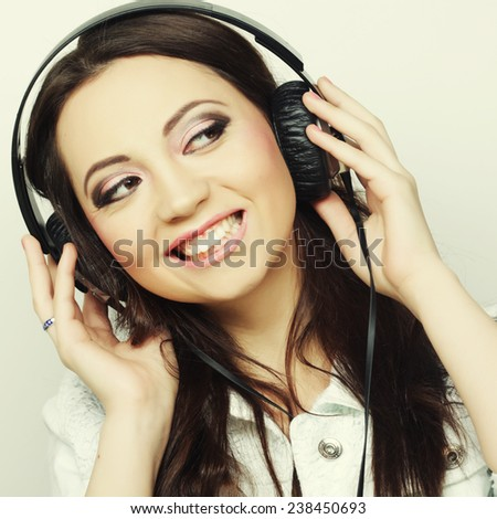 Young happy woman with headphones listening music  - stock photo