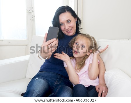 young happy woman with her little cute blond daughter taking selfie photo with mobile phone enjoying together at home sofa couch in mother and little girl self portrait picture concept - stock photo