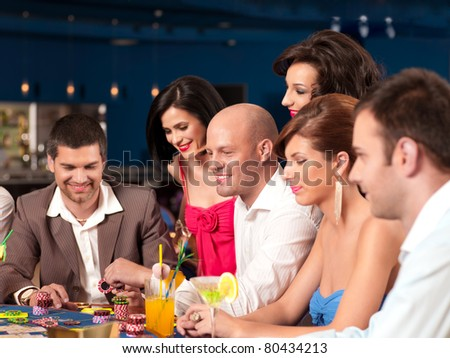 young happy women and men playing blackjack - stock photo