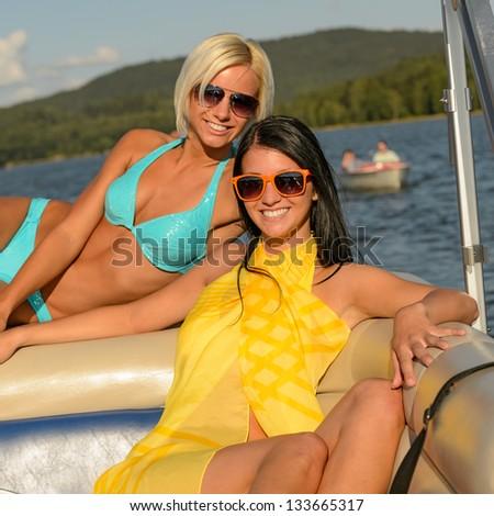 Young happy women sunbathing on boat enjoying summer - stock photo