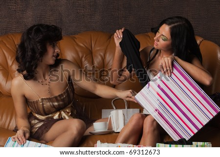 Young happy women with shopping bags sit on leather sofa at home. Sale. - stock photo
