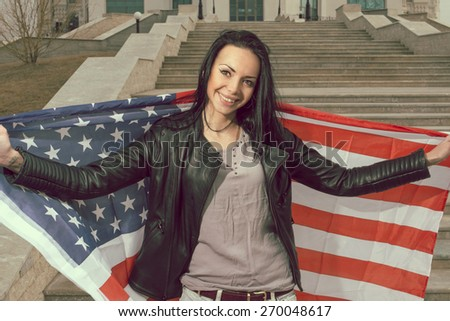 Young happy women with us flag outdoors smiling widely. - stock photo
