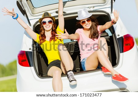 Young happy young woman sitting in car trunk outdoor - stock photo