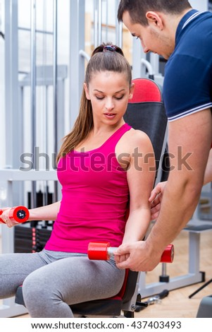 Young, healthy, attractive adult girl performing biceps muscle workout with professional, personal instructor / trainer at the gym on a bench. - stock photo