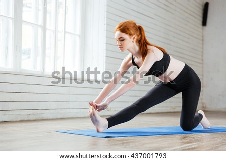Young healthy fitness woman doing stretching exercise in the gym - stock photo