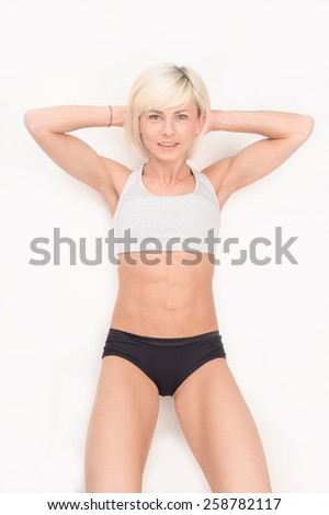 young healthy girl resting after a workout on the floor. on white isolated background - stock photo