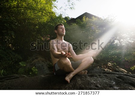 young healthy man doing yoga relaxation outside  - stock photo