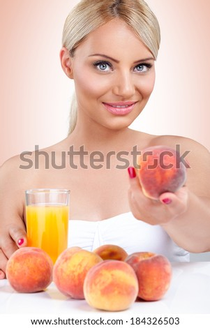 Young healthy woman with natural peach juice - stock photo