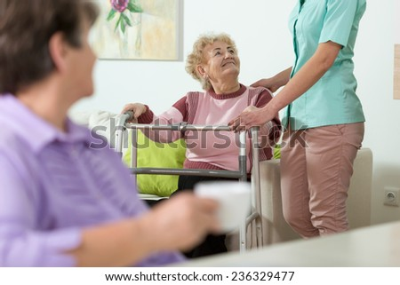 Young helpful nurse and older woman with walker - stock photo