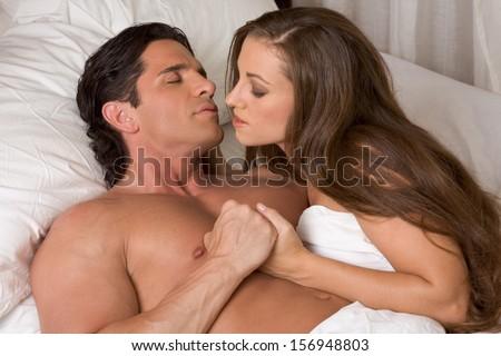 young heterosexual couple in bed - stock photo